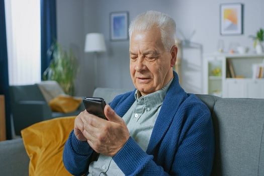 Portrait of Progressive Senior Man Sitting in His Living Room Easily Uses Smartphone, Does Touching Gestures and Feels Very Comfortable with New Technologies.