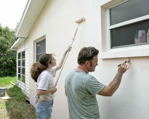 a girl and boy painting exterior of house