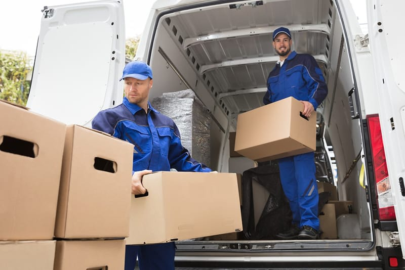 two boys in blue dress moving packed things